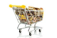 Carro de compras con las monedas Foto de archivo libre de regalías
