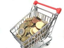 Carro de compras con las monedas Imágenes de archivo libres de regalías