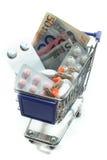 Carro de compras con las píldoras y el dinero Imagen de archivo libre de regalías