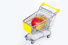 Carro de compras con una manzana grande Imagen de archivo libre de regalías