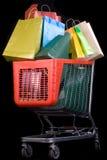 Carro de compras por completo de regalos en fondo negro Fotografía de archivo