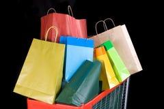 Carro de compras por completo de regalos en fondo negro foto de archivo libre de regalías
