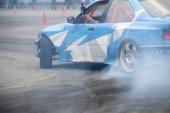 Carro de derivação no fumo dos pneus ardentes na trilha no movimento Imagens de Stock