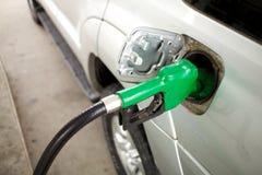 Carro de enchimento da mangueira verde da gasolina fotografia de stock