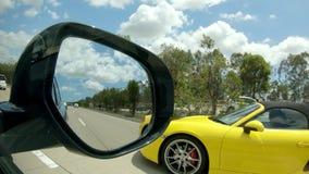 Carro de esportes amarelo na opinião da estrada do mirrorl do lado do carro filme