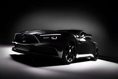 Carro de esportes preto moderno em um projetor em um fundo preto Fotos de Stock Royalty Free