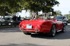 Carro de esportes vermelho clássico velho conduzido na estrada Fotografia de Stock Royalty Free