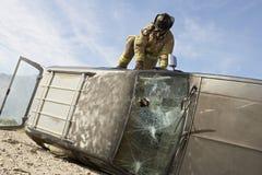 Carro de Getting Into Crashed do sapador-bombeiro imagem de stock royalty free