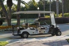 Carro de golf vacío que se sienta en una trayectoria del macadán por a Foto de archivo