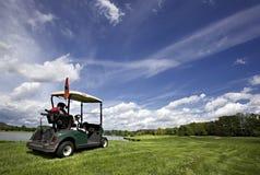 Carro de golfe no campo de golfe e no céu nebuloso maravilhoso Imagem de Stock Royalty Free
