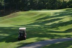 Carro de golfe no curso da manhã fotografia de stock royalty free