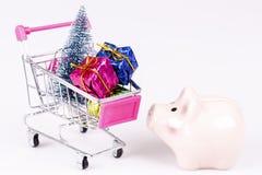Carro de la compra con el árbol de navidad, los regalos y la caja de dinero del cerdo imagenes de archivo