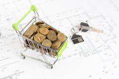 Carro de la compra con el dinero en el proyecto de la casa Foto de archivo libre de regalías