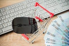 Carro de la compra con el ratón delante del teclado de ordenador Fotografía de archivo libre de regalías