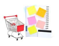 Carro de la compra con la tarjeta y el cuaderno de crédito Imagen de archivo libre de regalías