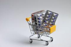 Carro de la compra con las cápsulas Fotos de archivo libres de regalías
