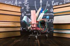 Carro de la compra con las fuentes de escuela, en la tabla con los libros contra la perspectiva de una pizarra Concepto de nuevo  foto de archivo
