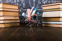 Carro de la compra con las fuentes de escuela, en la tabla con los libros contra la perspectiva de una pizarra Concepto de nuevo  imagen de archivo libre de regalías