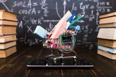 Carro de la compra con las fuentes de escuela, en la tabla con los libros contra la perspectiva de una pizarra Concepto de nuevo  imagenes de archivo