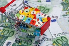 Carro de la compra con los signos de interrogación en cientos billetes de banco euro Foto de archivo libre de regalías