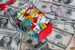 Carro de la compra con los signos de interrogación en billetes de banco de los dólares Fotos de archivo