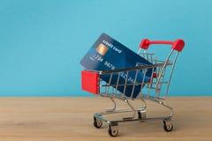 Carro de la compra con la tarjeta de crédito en fondo azul Fotografía de archivo