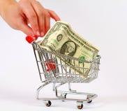 Carro de la compra, dinero y mano Fotografía de archivo libre de regalías