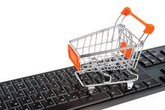 Carro de la compra en el teclado negro aislado en blanco imagenes de archivo