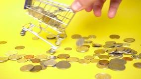 Carro de la compra en un fondo amarillo con las monedas de los pa?ses diferentes almacen de video