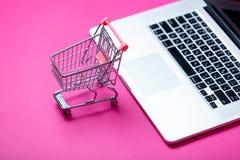 Carro de la compra hermoso y ordenador portátil fresco en los vagos rosados maravillosos foto de archivo