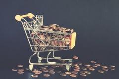 Carro de la compra llenado de las monedas de oro Fotografía de archivo libre de regalías