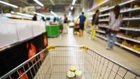 Carro de la compra móvil en un supermercado grande metrajes
