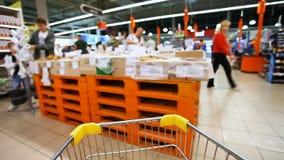 Carro de la compra móvil en un supermercado grande almacen de metraje de vídeo