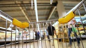 Carro de la compra móvil en un supermercado grande almacen de video