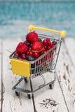 Carro de la compra miniatura con las fresas, los arándanos y redcu Fotografía de archivo libre de regalías