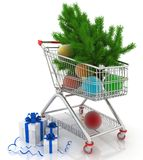 Carro de la compra por completo con las bolas de la Navidad con las cajas del abeto y de regalo Foto de archivo libre de regalías