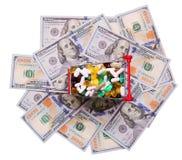 Carro de la compra por completo con las píldoras sobre billetes de dólar Foto de archivo