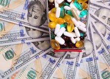 Carro de la compra por completo con las píldoras sobre billetes de dólar Imágenes de archivo libres de regalías