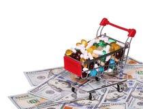 Carro de la compra por completo con las píldoras sobre los billetes de dólar, aislados Fotos de archivo