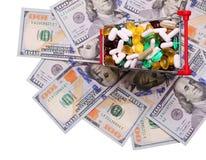 Carro de la compra por completo con las píldoras y las cápsulas sobre billetes de dólar Foto de archivo libre de regalías