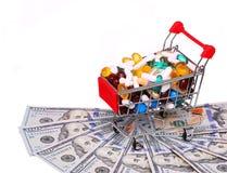 Carro de la compra por completo con las píldoras sobre los billetes de dólar, aislados Imágenes de archivo libres de regalías