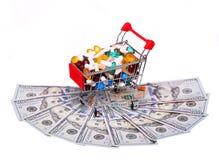 Carro de la compra por completo con las píldoras sobre los billetes de dólar, aislados Fotografía de archivo libre de regalías