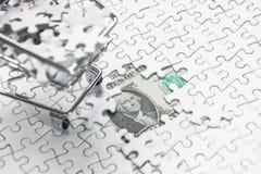 Carro de la compra por completo del rompecabezas en fondo del dólar del dinero, fotografía de archivo libre de regalías