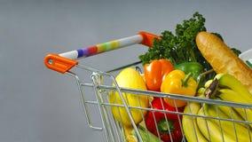Carro de la compra por completo de verduras, de frutas y del pan imágenes de archivo libres de regalías