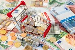 Carro de la compra que se coloca en billetes de banco euro Fotografía de archivo libre de regalías