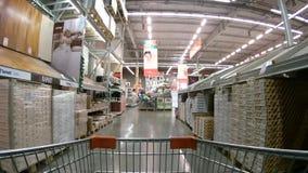Carro de la compra que se mueve entre los estantes con los materiales de construcción almacen de metraje de vídeo