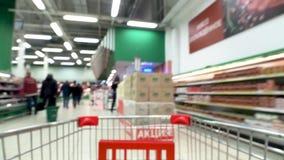 Carro de la compra que se mueve entre los pasillos del supermercado metrajes