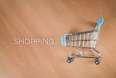 Carro de la compra y al lado de él las compras de la palabra fotos de archivo