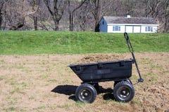Carro de la yarda por completo con las hierbas y la suciedad Imagenes de archivo