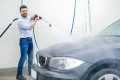 Carro de lavagem do homem na estação da lavagem de carros Fotografia de Stock